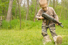 Little boy playing with a gun in the countryside Stock Photography