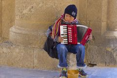 Little boy playing harmonica in Rhodes town, Greece. Greek boy earning money by playing an instrument on the street of Rhodes town, Greece Stock Photography
