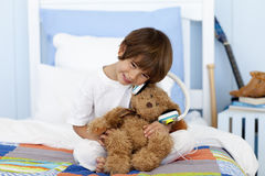 Little boy playing with headphones and teddy bear Royalty Free Stock Images