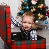 Little boy playing hiding in a red plaid suitcase in the interio Royalty Free Stock Images
