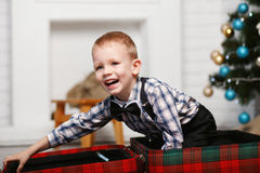 Little boy playing hiding in a red plaid suitcase in the interio Stock Photography