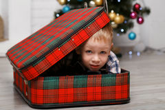 Little boy playing hiding in a red plaid suitcase Royalty Free Stock Photo
