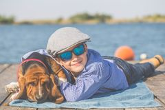 Little boy playing with his dog Basset Hound by the river. Little cute boy with a cap lying by the river with his dog. They enjoy together on a beautiful sunny royalty free stock images