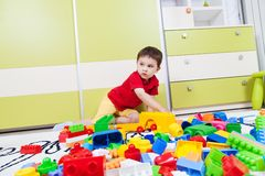 Little boy playing with his plastic cubes royalty free stock images
