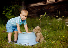Little boy playing with his teddy bear outdoors Royalty Free Stock Image