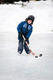 Little boy playing hockey on an outdoor rink. Five year old boy wearing a helmet playing hockey on an outdoor ice skating rink Royalty Free Stock Photo
