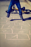 Little boy playing hopscotch with bike outside Royalty Free Stock Photography