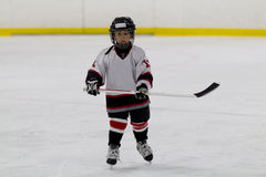 Little boy playing ice hockey Stock Photos