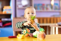 Little boy playing indoors at home or kindergarten. Adorable child with plastic vegetables and fruits. royalty free stock photo