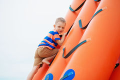 Little boy playing on an inflatable playground on the beach Stock Photos