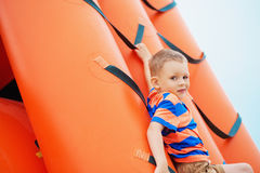 Little boy playing on an inflatable playground on the beach Royalty Free Stock Photography