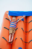Little boy playing on an inflatable playground on the beach Royalty Free Stock Images