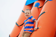 Little boy playing on an inflatable playground on the beach Royalty Free Stock Image