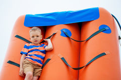 Little boy playing on an inflatable playground on the beach Royalty Free Stock Photo