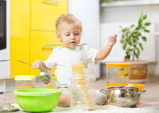 Little boy playing with kitchenware and foodstuffs. Child little boy playing with kitchenware and foodstuffs in kitchen Royalty Free Stock Images