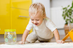 Little boy playing with kitchenware and foodstuffs in kitchen. Playful child boy with kitchenware and foodstuffs on floor in kitchen stock image