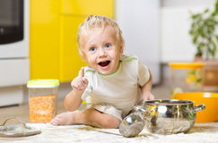 Little boy playing with kitchenware and foodstuffs. Playful child boy with kitchenware and foodstuffs on floor in kitchen royalty free stock photography