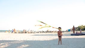 Little boy playing with a kite on the beach in summer. the kite flies against the blue sky and the boy draws him to. Himself with a cord stock video footage
