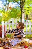 Little boy playing with  leaves and eating cookies in the autumn Stock Photos