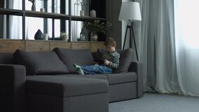 Little boy playing on line game on digital tablet. Cute preschool boy playing on line game on digital tablet pc while sitting on the couch in domestic room stock video footage
