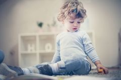 Little boy playing in living room. Little boy playing in living room alone and sitting on floor Stock Photo