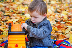 Little boy playing with the machine in the park on yellow leaves Stock Image