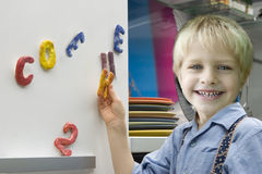 Little boy playing magnetic letters Stock Photography