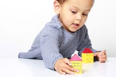Little boy playing with miniature toy block houses royalty free stock images
