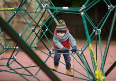 Little boy playing on modern kids play ground stock image