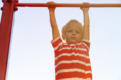 Little boy playing on monkey bars in playground Royalty Free Stock Image