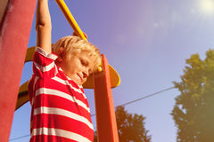 Little boy playing on monkey bars in playground Royalty Free Stock Photo