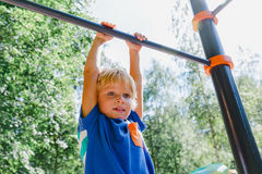 Little boy playing on monkey bars at playground stock photos