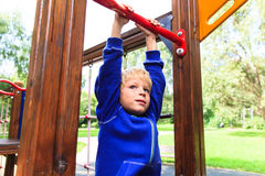 Little boy playing on monkey bars at playground Stock Image