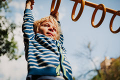 Little boy playing on monkey bars at playground Royalty Free Stock Photo