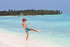 Little boy playing in the ocean on tropical beach Stock Images