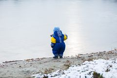 Little boy playing outdoor on frozen lake shore. Stock Images