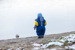 Little boy playing outdoor on frozen lake shore. Stock Photography