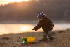 Little boy playing outdoor with a toy car. Stock Photos