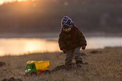 Little boy playing outdoor with a toy car. Royalty Free Stock Image