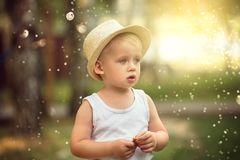 Little boy playing in park. Little boy playing in park in a sunny day. Baby in a fashionable hat. Happy childhood royalty free stock image