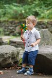 Little boy playing in park with windmill pinwheel royalty free stock images