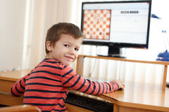 Little boy playing on PC chess looking back stock image