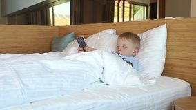 A little boy playing phone at home was lying on the bed under the blanket. Slow motion. Telephone addiction stock footage