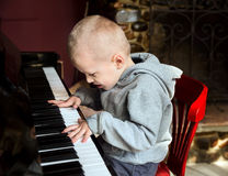 Little boy playing the piano Stock Photos