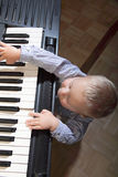 Little boy playing piano indoor Stock Images