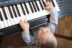 Little boy playing piano indoor Stock Photography