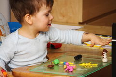Little boy playing with the plasticine on the glass pad. Little boy playing with the plasticine animals and figures on the glass pad Stock Images