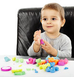 Little boy playing with plasticine. Happy caucasian toddler boy playing with clay dough, isolated on white background Royalty Free Stock Photography