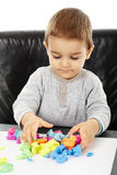 Little boy playing with plasticine. Happy caucasian toddler boy playing with clay dough, isolated on white background Royalty Free Stock Images