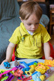 Little boy playing with plasticine. At home, thinking about what shapes he will make out of it Stock Photos